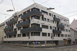 Wohnhaus mit schwarzen Balkonen, Oberleitungen, Wien