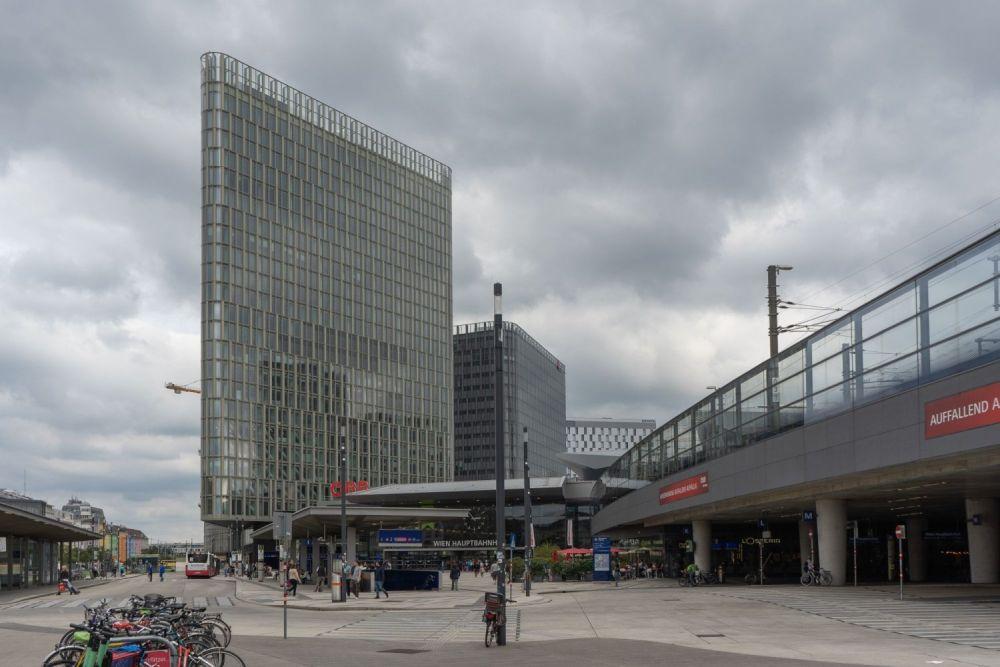 """Hauptbahnhof Wien, Südtiroler-Platz, Bürohaus """"The Icon Vienna"""", Asphalt, Bahntrasse, dichte Wolkendecke"""