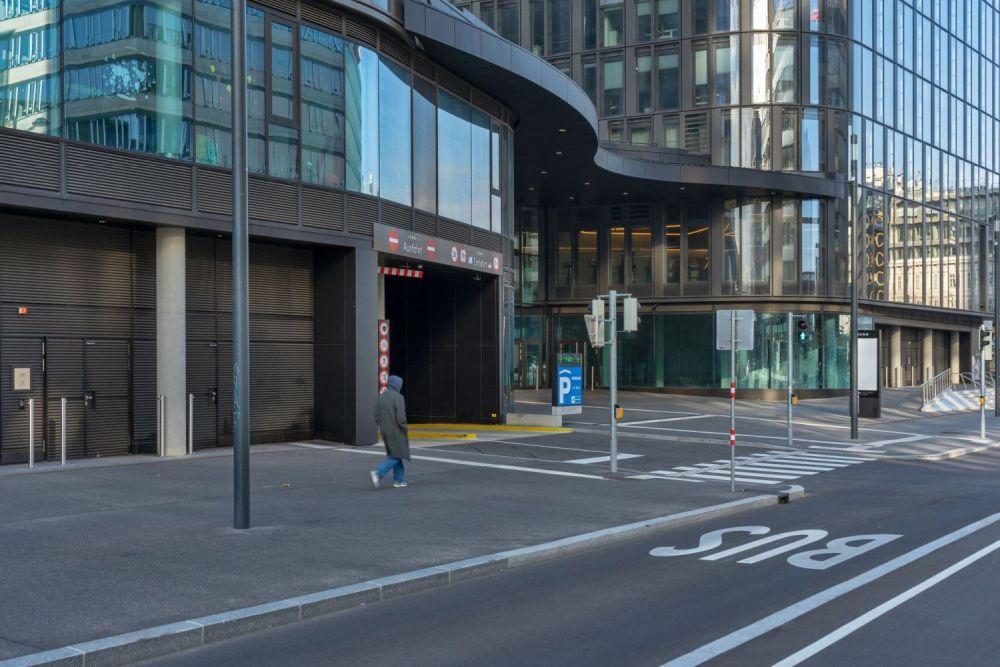 Asphaltfläche beim Wiener Hauptbahnhof, verlängerte Gertrude-Fröhlich-Sandner-Straße, Bürohaus mit Glasfassade, Einfahrt, Busspur, Fußgänger