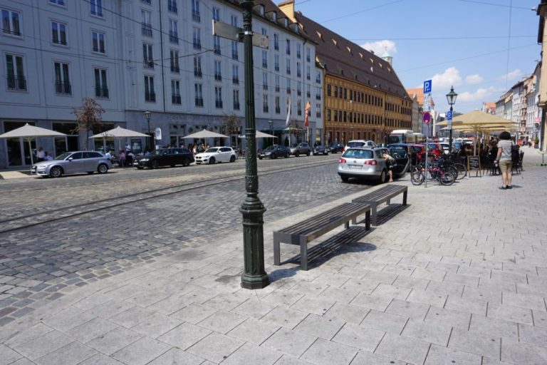 Straße mit historischen Gebäuden und Pflastersteinen in Augsburg, Straßenlaternen, Autos
