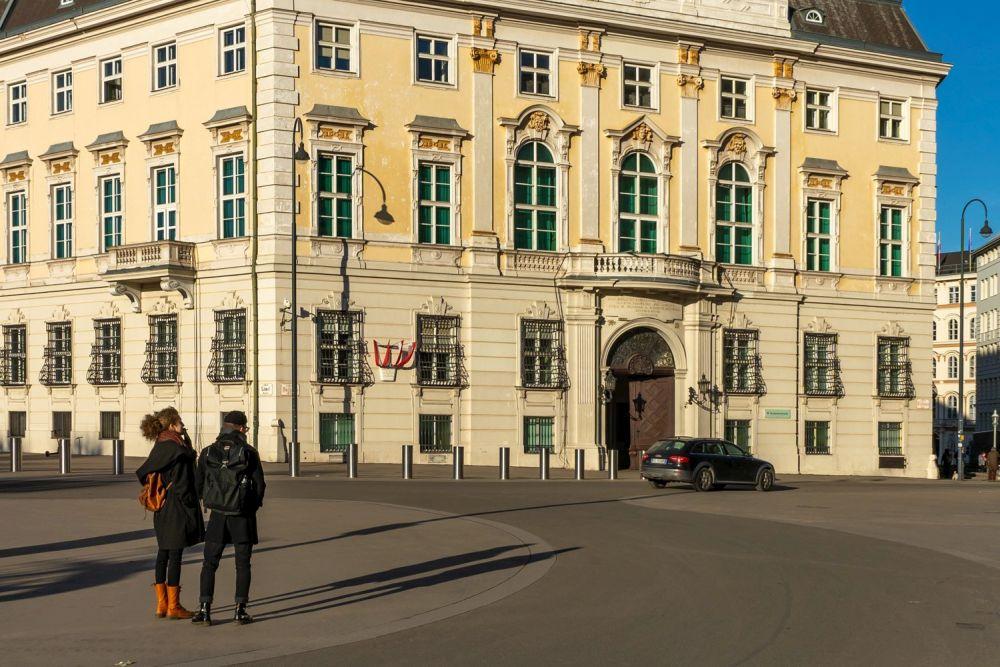 zwei Personen stehen am Ballhausplatz vor dem Bundeskanzleramt, Wien, Innere Stadt