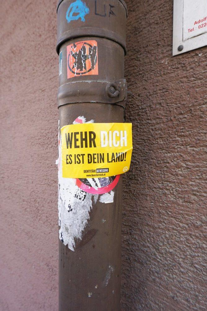 Aufkleber der Identitären und der Sozialistischen Jugend auf einer Regenrinne in der Baumgasse, Wien, 3. Bezirk