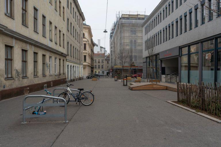 Autofreier Schulvorplatz in der Gasgasse, Asphaltfläche, Bäume, 1150 Wien