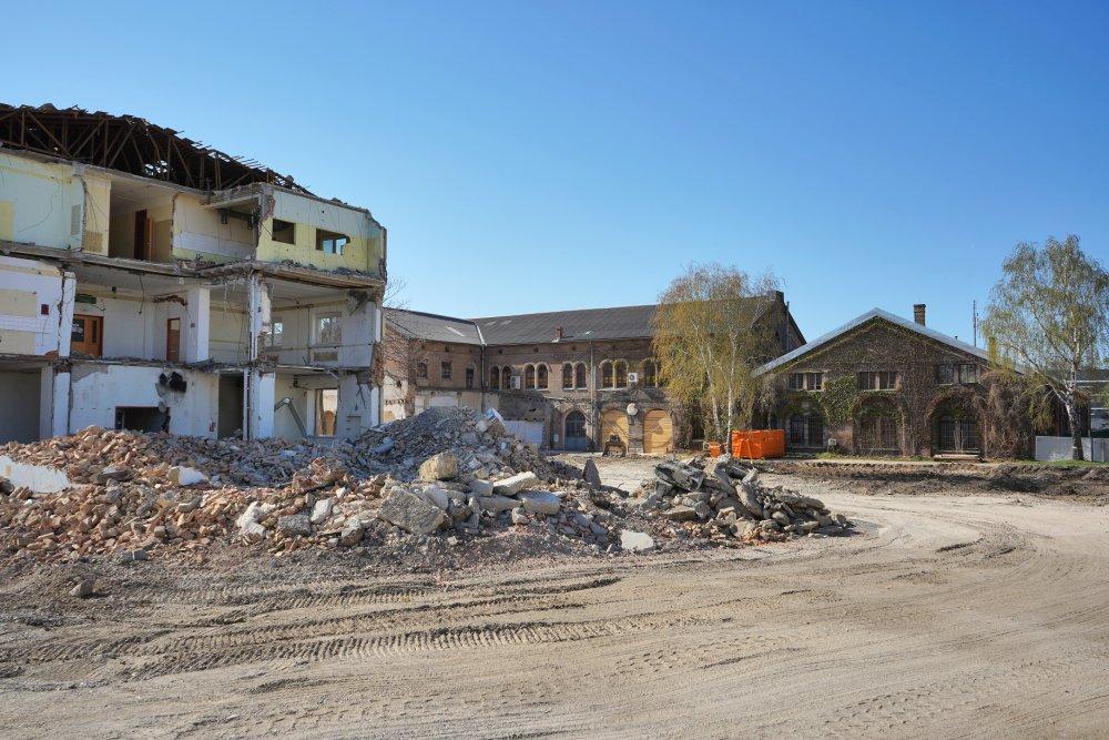 Neues Landgut während des Abrisses eines ÖBB-Bürohauses, Wien-Favoriten, Backsteinhallen, Nachkriegsgebäude, Schutt, Bäume, Baustelle