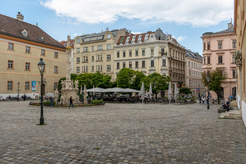 historische Gebäude, Denkmal und alte Straßenlaternen am Jodok-Fink-Platz in Wien-Josefstadt