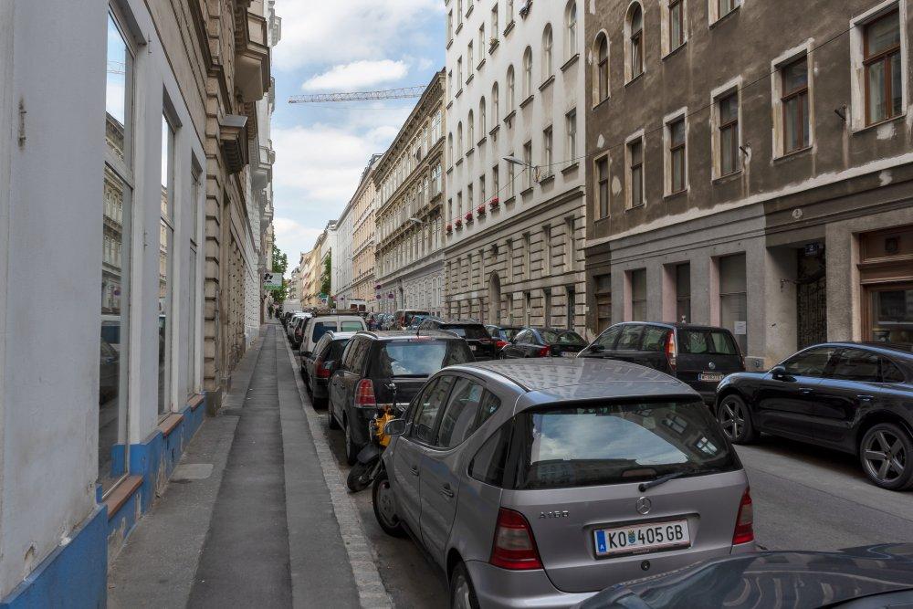 Gasse mit parkenden Autos und alten Häusern in Wien