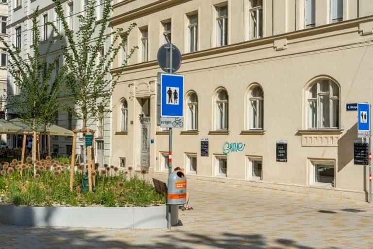 Fußgängerzone in der Königsegggasse, Bäume, Blumen, Verkehrsschilder, Gründerzeithäuser