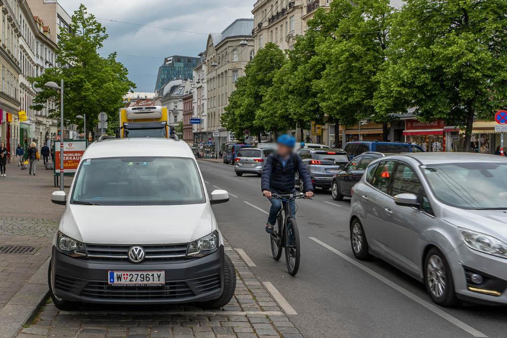 Radfahrer zwischen parkenden und fahrenden Autos auf der Landstraßer Hauptstraße, 1030 Wien