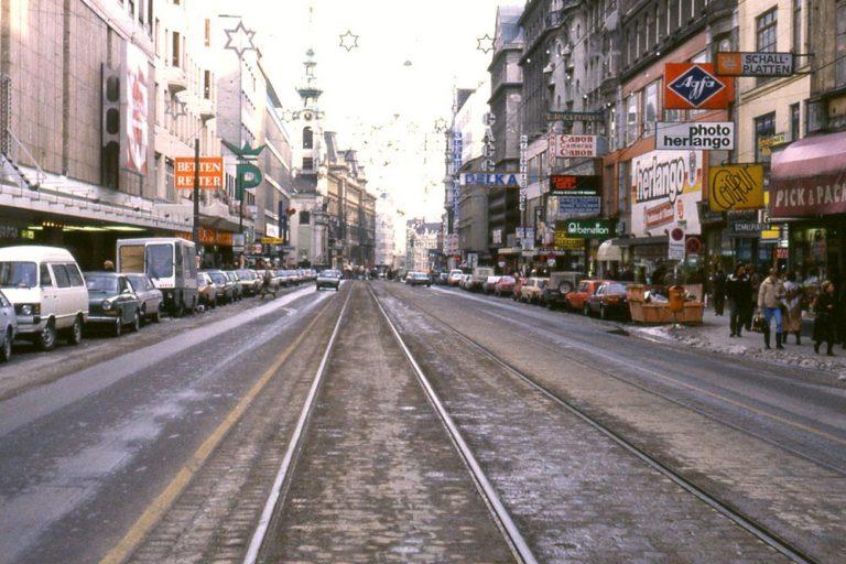 Mariahilferstraße mit Autoverkehr, Parkplätzen und Straßenbahnschienen, bei der Stiftgasse, Stiftskirche, Wien