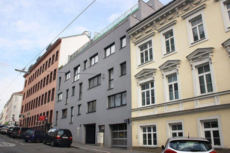 Wohnhaus in Ottakring mit grauer Fassade, in Schutzzone, erbaut nach Abriss eines Gründerzeithauses, nahe Thaliastraße
