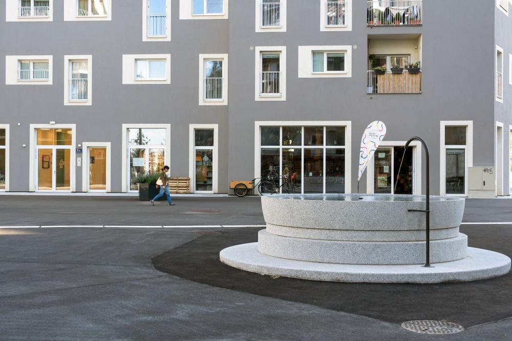Fußgängerzone in der Seestadt Aspern, Brunnen, Geschäft, Fußgängerin, Rad