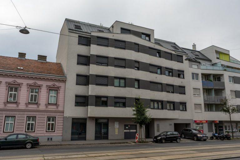 Neubau mit grau-gestreifter Fassade in Wien, Kagran, Donaustadt, neben Gründerzeithaus