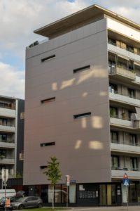 Neubau-Wohnhaus im Sonnwendviertel in Wien-Favoriten, kleine Fenster, Metallfassade, Baum, Verkehrszeichen