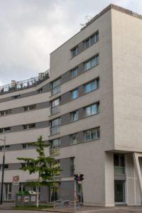 Neubau-Wohnhaus im Sonnwendviertel in Wien-Favoriten, graue Fassade, Baum, Ampel