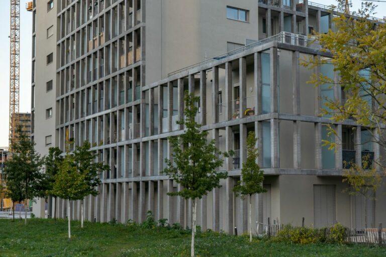 Wohnhaus in der Maria-Lassnig-Straße, Sonnwendviertel, am Helmut-Zilk-Park, Favoriten, Wien, Erdgeschoß, Bäume, Rasen, Gitter, Sichtbeton