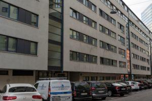 Wohnhausanlage in Favoriten, graue Fassade, parkende Autos, ÖBB-Zentrale, nahe Hauptbahnhof, Wien