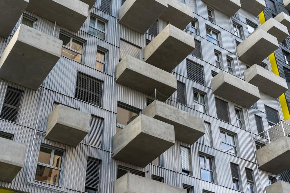 Fassade mit auskragenden Balkonen aus Sichtbeton, grauem Wellblech und großen Fenstern, Seeparkquartier, Donaustadt, Wien