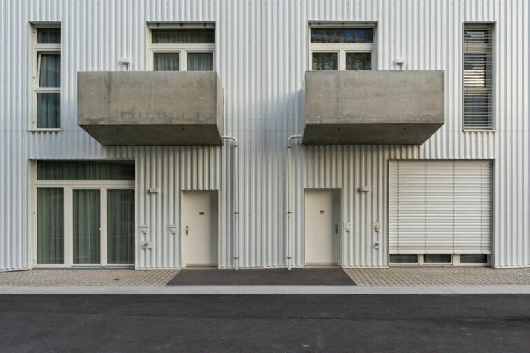 """Asphalt, Blechfassade, Erdgeschoßzone, Lydia-Sicher-Gasse, Wohnhaus """"Lakeside"""", Seestadt Aspern, Donaustadt, Wien"""