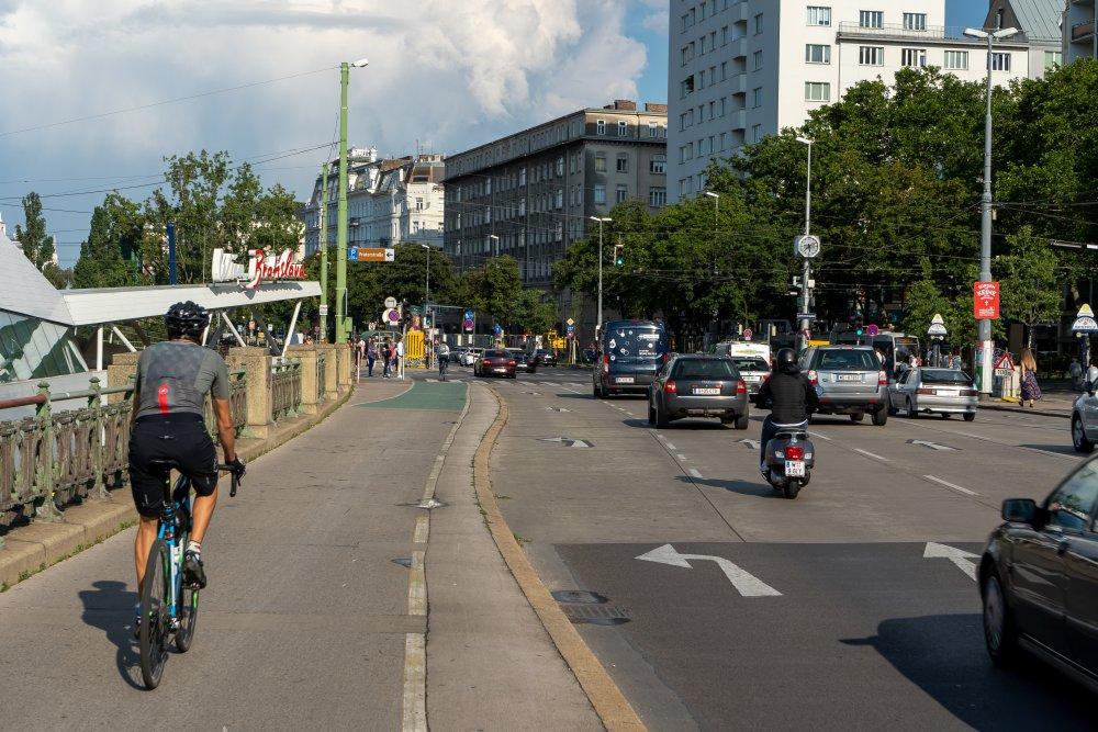 Radfahrer und Autoverkehr am Schwedenplatz in Wien