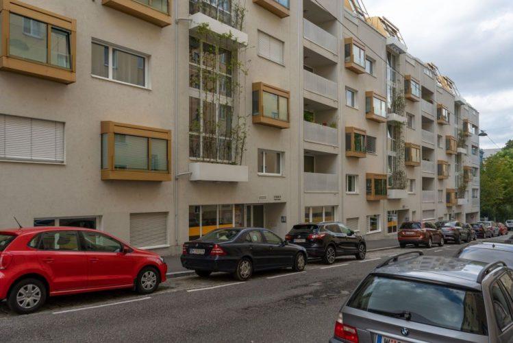 Haus mit Loggien, Fassadenbegrünung, parkende Autos