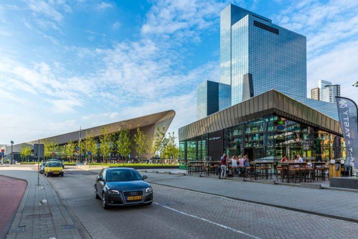 Rotterdamer Hauptbahnhof mit Hochhäusern und Auto
